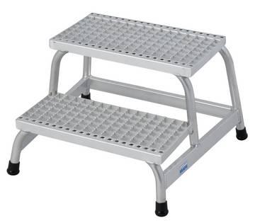 Wytrzymałe montażowe schodki aluminiowe z głębokimi antypoślizgowymi stopniami i dużą platformą dedykowaną pracom w obszarach o zwiększonym ryzyku poślizgnięcia się.