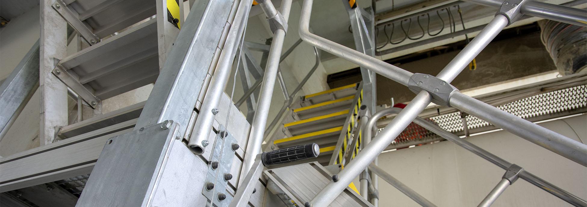 Stacjonarne schody z platformą z dodatkowo odchylanymi stopniami do obsługi pojazdów silosowych o różnej wysokości